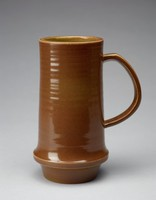 Heavy mug with cylindrical, slightly waisted form that flares out to a ridge and then tapers towards the base. The mug's exterior is glazed brown and the exterior ridges appear white. The mug has thin horizontal, impressed lines circling the form. The interior is glazed green and also has imprinted, thin lines.