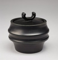 Sugar bowl with a bucket shape that flares out twice and tapers in towards the base. The exterior is matte black with some slight impressed banding visible on the body. The lid is circular with an exaggerated 'u' shape in its center.
