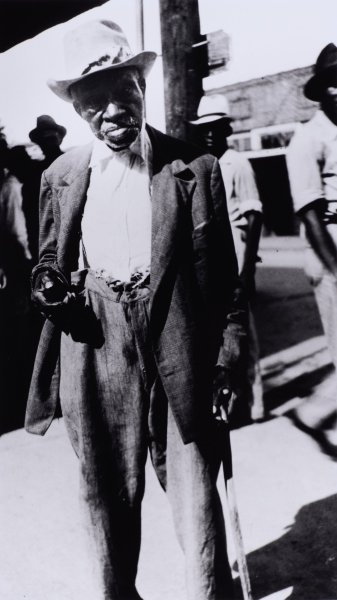 This black and white photograph shows an elderly man leaning on a cane held in his left hand with his right hand raised to hip height. He is wearing a brimmed hat, blazer, white shirt, and oversized pants. In the background is a cityscape, and at least three other obscured figures.