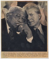 """Black and white press print of two older men, one white and one African American, talking two each other with their heads bent close together. Both men wear dark suits and ties. Includes caption """"(AX3) ATLANTA, Ga., Jan. 15--WITH HEADS TOGETHER--The Rev. Martin Luther King Sr. and President Jimmy Carter (right) share words during Sunday's ceremony in Atlanta to present the Dr. Marting Luther King Jr. Non-Violent Peace Prize to President Carter. (AP LASERPHOTO) 1979 (cab205 oostf/jw)"""""""