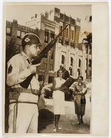"""Black and white press print of a National Guardsman (left) standing in front of a multiple story high school building while two white girls in dresses look on from behind. Includes caption """"On Guard, Little Rock, Arkansas: A National Guardsman continues his vigilance at the Central High School in Little Rock to bar entrance to Negroes. It was the second day in a row guardsman were stationed around the school on orders of Gov. Orval Faubus. The Justice Department has ordered a full probe in Little Rock for the Federal Judge whose integration order has twice been ignored."""""""