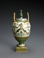 """Vase of bone china in the shape of the First Day's Vase with bulbous body and small foot resting on a small square plinth, with two upright, elongated handles, the flat cover with baluster finial, the vase in the """"Aesthetic style"""" and elaborately decorated on a white ground with two large inward curling scrolls on all four sides in shades of matte olive green, turquoise, and gold, in between are leafy swags extending from orange and gold rectangular reserves above a stylized acanthus leaf element, the lower body in matte olive green with cross hatching and parallel lines in gold, the shoulder of the vase with gold anthemion motifs against a matte olive green ground, the handles gold and the foot decorated with a band of leafy elements in orange and turquoise, a similar band runs around the side of the cover, the top of the cover and the finial in matte olive green highlighted in gold, the square base matte green on the sides and likewise highlighted in gold."""