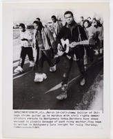 """Press print with caption """"(MRX3) MONTGOMERY, Ala., March 24 - (AP)-Jimmy Collier of Chicago strums guitar as he marches with civil rights demonstrators enroute to Montgomery today. Marchers have shoes encased in plastic because of past rainy weather. They hope to arrive in Montgomery late tonight for rally Thursday. (APWirephoto) 1965"""""""
