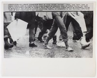 """Press print with caption """"(SEX-6) SELMA, ALA., MARCH 23--MARCHING FEET IN CIVIL RIGHTS PROTEST -- Feet, some bare, some in tennis shoes, some in combat boots, wrapped in plastic, some in rubber boots, all move over a rain-soaked highway in today's third lap of the civil rights march on Alabama's capital at Montgomery. The march, in protest of voting rights, is scheduled to end Thursday. (APWirepho / (SEE AP WIRE STORY) (wfa 2 1310 stf)1965"""""""