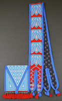 Beaded bag with triangular shaped flap folded over opening, and shoulder sash with forked ends. Yarn tassels with cloisonné beads attached to bottom of bag, and ends of sash.
