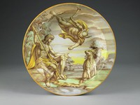 Large, deep creamware charger painted in bright enamel colors in shades of yellow, green, brown, and blue, the front rim edged in yellow and the center with a scene that extends to the rim of Mercury floating from above, his right arm outstretched, towards a seated Paris, who extends his left arm with hand open to receive the Apple of Discord, on the right a seated puma looks on, in a rocky landscape with trees and a river edge in foreground; the reverse decorated with a band of zigzags in browns and blues interspersed with yellow and green circular motifs, with a green band and a blue band within which the artist's monogram, date 1858, and the inscription MERCVRIO presenta il pumo a PARIDE.