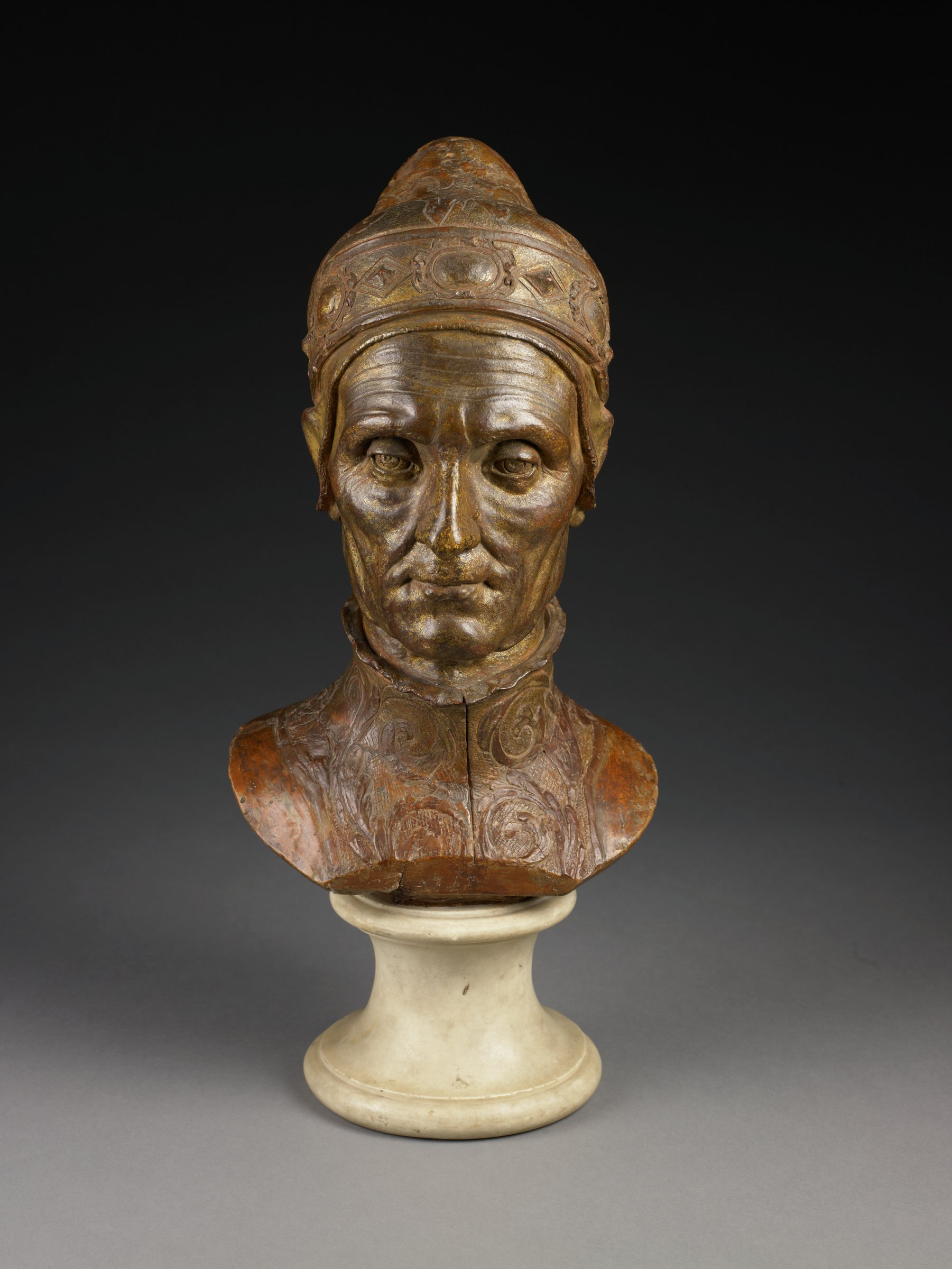 """This terracotta is a nearly life sized bust of the aging sitter. He wears the doge's official """"corno ducale,"""" with its jeweled rim and brocaded bonnet. Beneath the hat is a thin cap, carefully modeled over the ears. His garment is also brocaded, with a crimped collar. The Doge's face is lined with incised wrinkles, and modeled to give the appearance of sagging skin. The cornea and retina are also incised."""