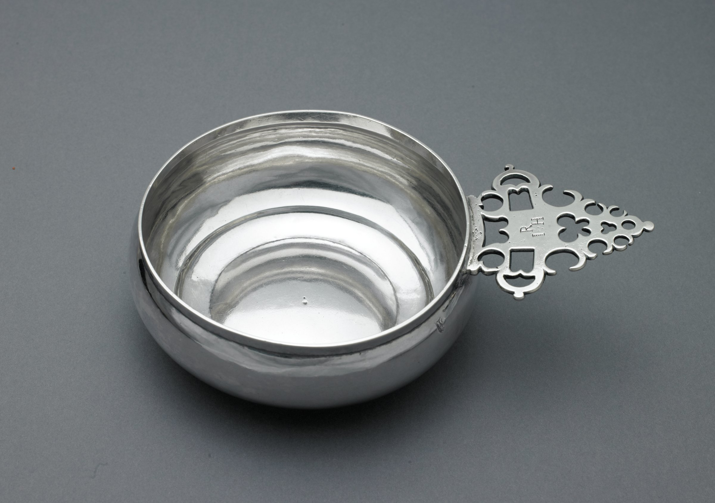 Silver porringer, a small bowl, typically with a handle, used for soup, stew, or similar dishes, of typical form comprised of a round  bowl with keyhole handle, engraved on the top of the handle with the initials R over I * H.