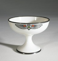 Whiteware dish with silver overlay trim around rim and foot; winged scarab motifs in silver overlay with green and orange overglaze enamel at 12 and 6 o'clock positions; Egyptian lotus motifs in silver overlay at 9 and 3 o'clock.