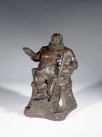 """Large, cast iron tobacco box in the form of a seated, bearded Sir John Falstaff wearing sixteenth-century garb with a large belt and ruffled collar in a scene from Shakespeare's  """"Henry IV"""" (act 2, scene 4) in which Falstaff pulls his dagger and proclaims """"…this chair shall be my state, this dagger my scepter…!""""  Falstaff is seated in an armchair whose armrests end in goat's heads, below the chair on either side is a bearded male mask; Falstaff's crossed feet rest on a small stool, the chair and stool rest on a base decorated with scrolls; his right arm is raised and his hand holds the handle of his dagger (the blade is broken off); his left arm rests on the chair's armrest while his left hand supports a long sword, which rests against his knee. The upper torso is hinged and opens to reveal the interior of the tobacco box."""