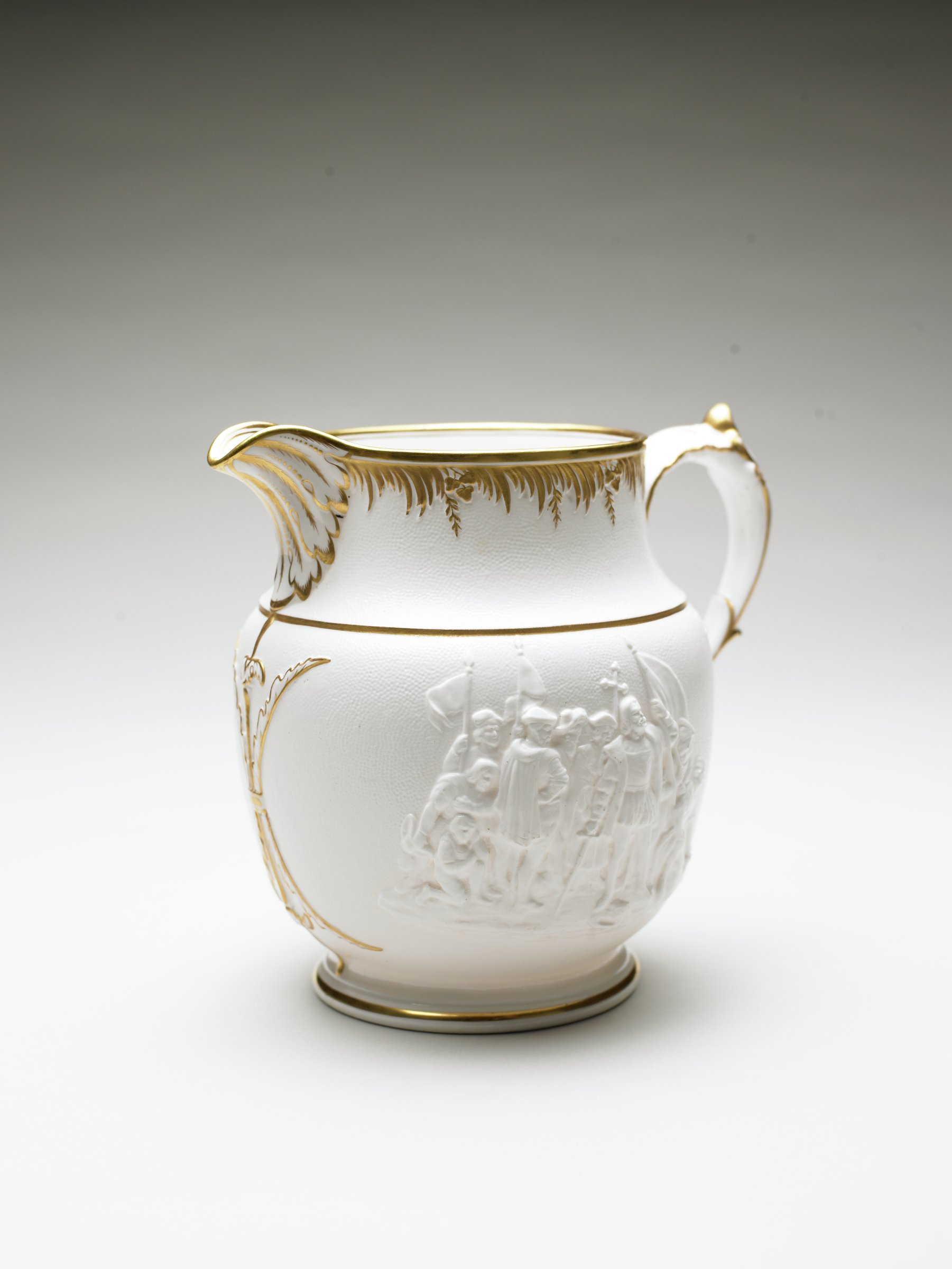 Large white stoneware pitcher of baluster form with leaf-molded spout and scrolled handle, the body with on both sides the same molded image in relief of Christopher Columbus and his crew landing in the New World, with gilt highlights around the lip, spout, handle, foot and shoulder.
