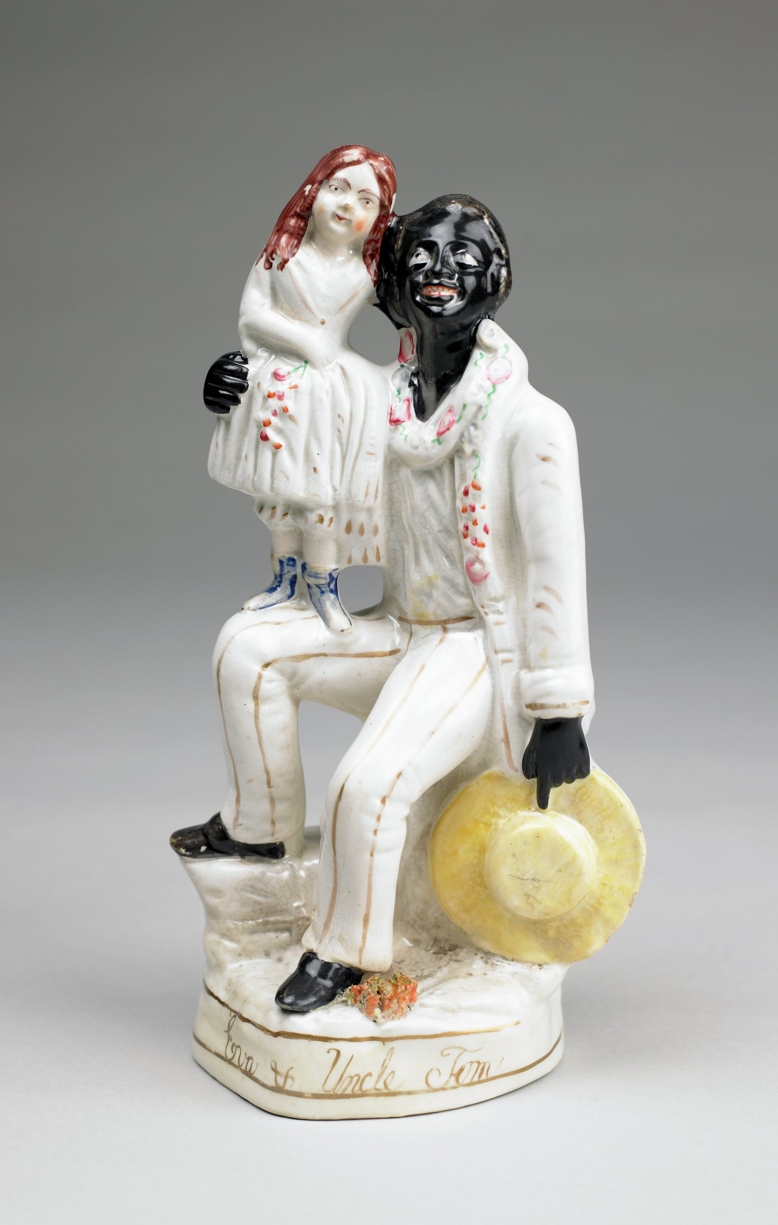 """Creamware flatback figural group of Uncle Tom and little Eva from """"Uncle Tom's Cabin,"""" Uncle Tom sits on a stump with his right foot resting on a wrapped package, he wears a white suit picked out in gold, his shoes, face and hands are glazed black, in his left hand he holds a yellow straw hat, around his neck is a floral garland, with a small sprig of foliage at his left foot, Eva stands on his right knee, she wears a white dress and holds a floral sprig in her right hand, her shoes are blue and her hair is brown, Uncle Tom's right hand is around Eva's waist, holding her on his knee, Eva's left arm is around Uncle Tom's neck, the base with two parallel gold lines and the names """"Eva & Uncle Tom"""" in script."""