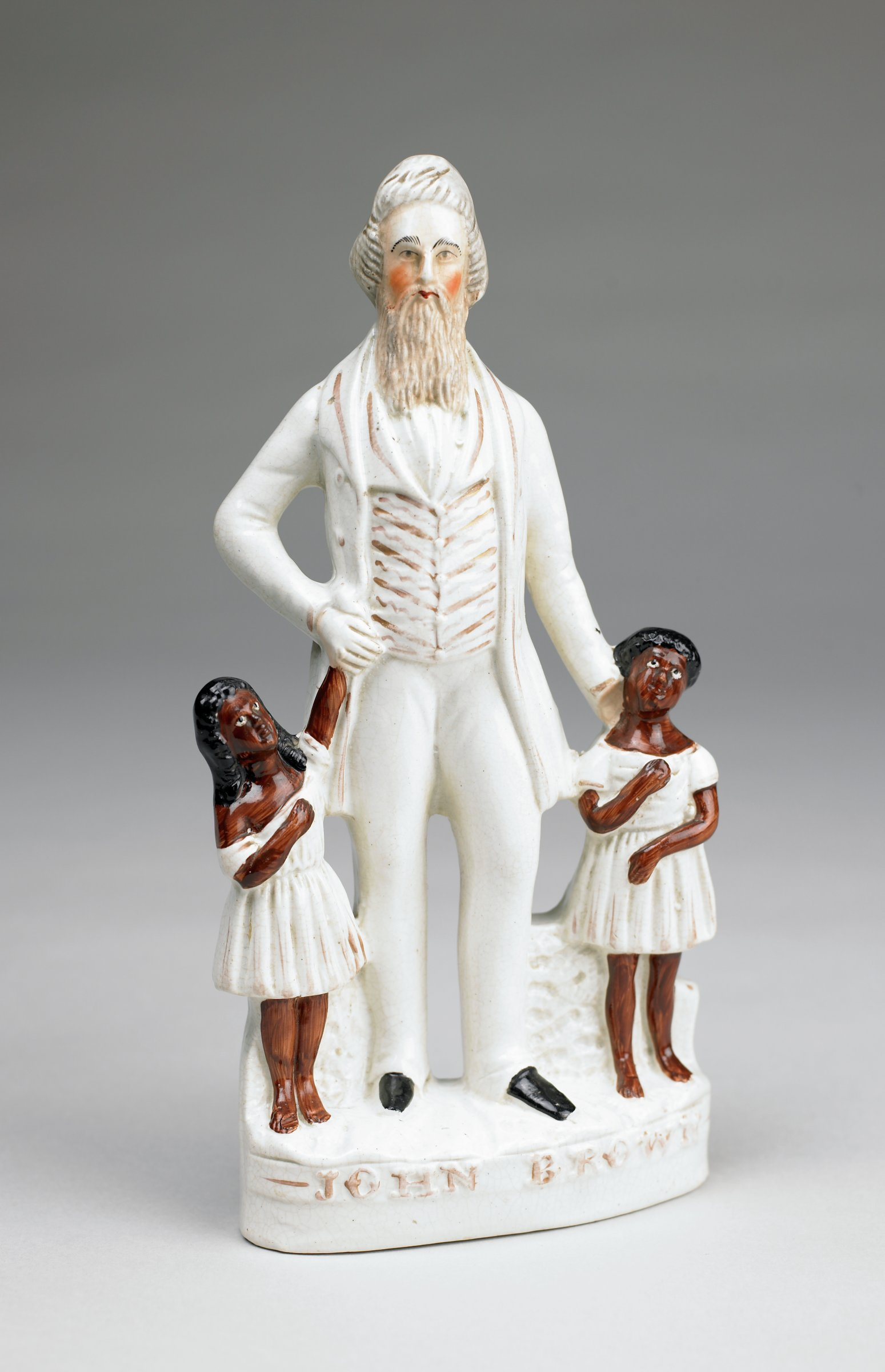 Tall creamware flat-back figural group of abolitionist John Brown with two small African-American girls in white dresses on an oval base with the name JOHN BROWN on the front, the skin of the girls glazed dark brown, the hair black, Brown's beard glazed brown and his cheeks rosy, otherwise his suit is white with details picked out in bronze lustre, his shoes black.