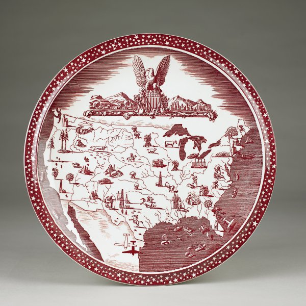 """Decoration transfer printed in maroon.  """"The key piece of the [""""Our America""""] series is the…chop plate that features, at top center, the national eagle above the American shield, the eagle's wings outspread over a city to the left and farmland to the right.  Below this group and covering most of the face of the plate, is an outline map of the United States that has small perspective drawings of items or activities common to each state or region.""""  (Source:  Maxine Feek Nelson, Collectible Vernon Kilns 2nd ed.  (Paducah, KY:  Collector Books, 2004), 234.)"""