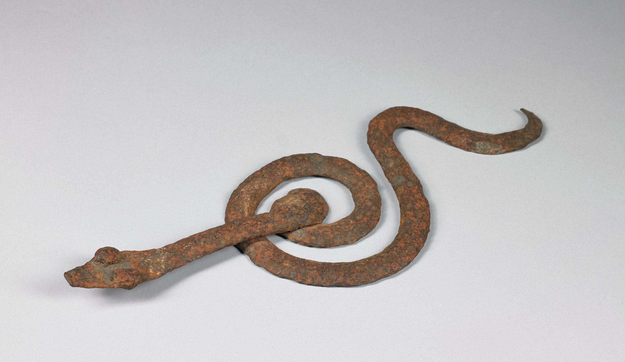 Flat serpent with head and tail emerging from central coil