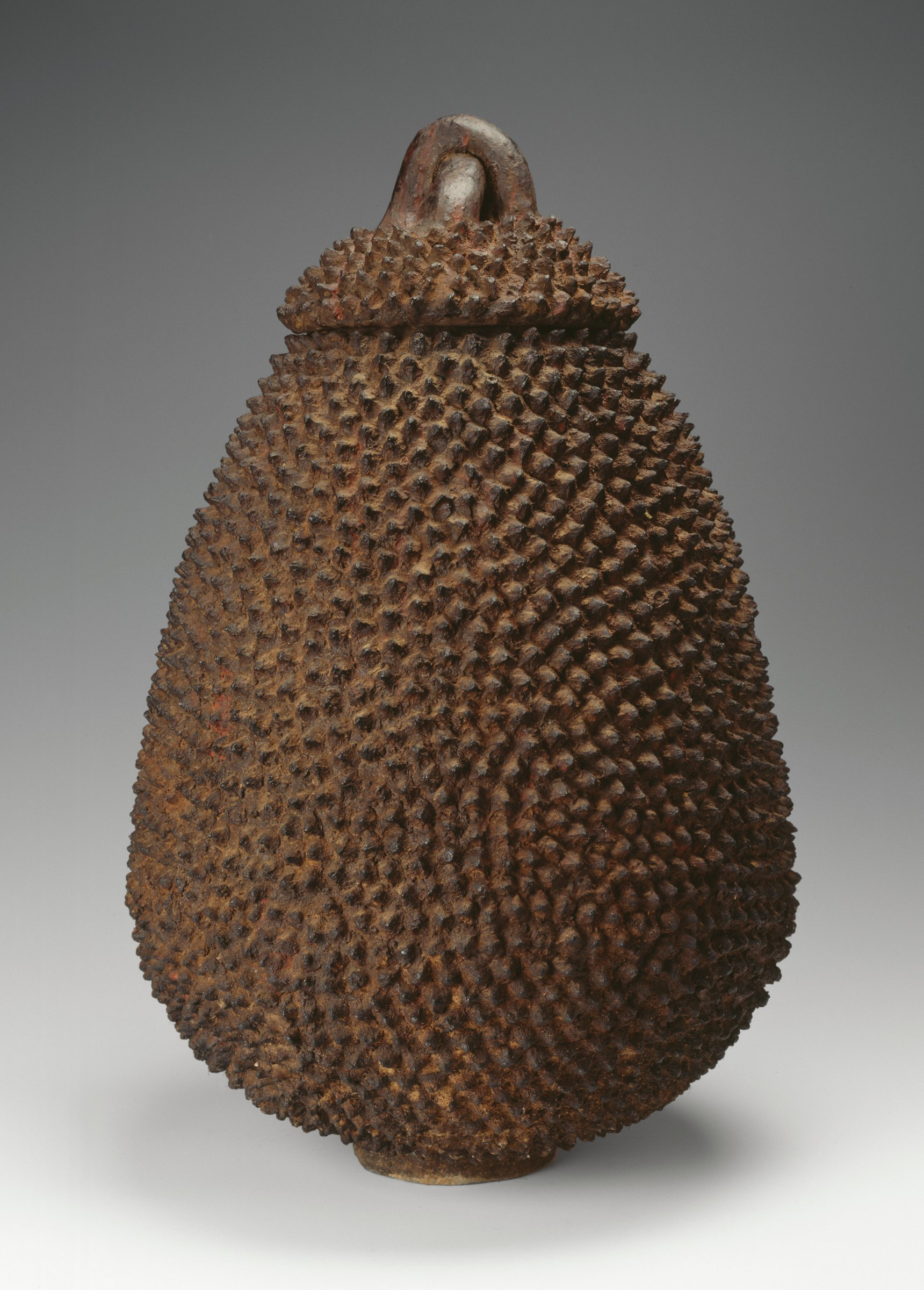Pear-shaped, dark-brown vessel covered with raised points; lid also covered with points, has handle formed with two cylindrical loops, one atop the other, forming a cross. Thick patination found between points.