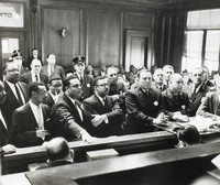 This black-and-white photograph shows the inside of a courthouse. Well-dressed black men stand at left and policemen stand at right.
