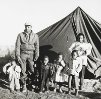 This black-and-white photograph features a portrait of a black family evicted from their home. The father (at left) and the mother (at right) stand before a tent with four children. The mother also cradles an infant in her arms.
