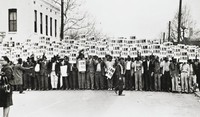 """The black-and-white photograph shows the Sanitation Workers Strike in Memphis, Tennessee on March 28, 1968. Black men hold up placards that read, """"I Am A Man"""" in the middle ground and background."""