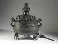 A large bronze vessel atop three mythical beasts that serve as feet; censer has a cover with separate finial and a ladle