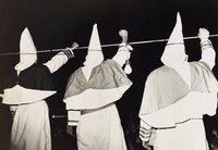Three robed Klansmen stand with raised fists in front of an audience.