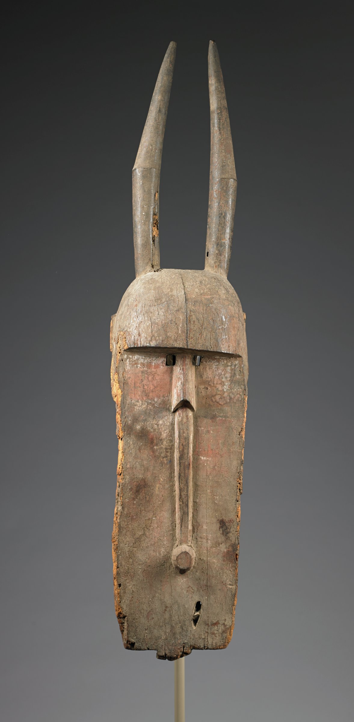 Helmet mask composed of long plank, heavy, hemispherical brow ridge, and tall, vertical, jointed horns. Small square eyes just below brow ridge on either side of the nose are pierced through the plank. Plank divided vertically by raised ridge extending from nose to raised umbilicus, located in bottom third of mask. No mouth is evident. Mask bears traces of symmetrical geometric patterns in red, black and white pigments.A sacred mask owned and worn solely by blacksmiths among the Bobo people; associated with the cult of Dwo.