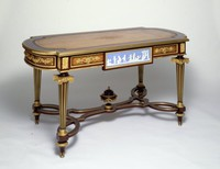 Elaborate Louis XVI-style center table veneered in lemon tree wood and rosewood, with reeded, tapering legs, ornamented with light blue jasper plaques with white relief depicting cupids at play and mercury-gilded bronze mounts, with interlaced stretchers with center urn topped with berry finial, and tooled leather surface
