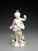 """One of a set of four large figures of soft-paste porcelain representing the """"Four Quarters of the Globe,"""" each depicted as a chubby child dressed in a costume deemed appropriate to his or her region and associated with symbols of the different continents.Europe: the figure of a female child wearing a white tunic decorated with flowers and cinched together with a yellow ribbon, over her shoulders she wears draped a yellow and red cloak, at her feet are symbols of the arts, sciences, and religion such as paintbrushes and a painter's palette, sheet music, books, and a bishop's miter scattered amongst flowers, in her right had she holds an orb, her left hand raised and outstretched, on her head a crown."""