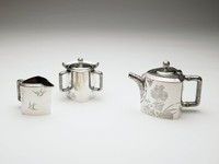 """Three-piece tête-a-tête tea set consisting of teapot, creamer and sugar, each piece three sided, the teapot with handle, finial and curved spout with overall embossed surface decoration of stylized leaf and berry design, the sides engraved with asymmetrical pattern of birds, butterflies and chrysanthemums, the border of applied """"Japanese chain"""" design (a pattern of painted ovals and half flowers with scrolls); the creamer with similarly embossed handles and finial, with beak-shaped spout, same border pattern, the body likewise decorated with engraved chrysanthemums and insects; the sugar with three embossed handles of same motif, the body engraved with insects and chrysanthemums, same border pattern, all pieces with the engraved initials: """"C.B.E."""" in the Japanese style"""