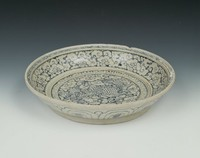 """Glazed stoneware dish with a mythical beast (called Qilin in Chinese) in center surrounded by """"ruyi"""" headed clouds, exterior with jeweled lappets all painted in underglaze blue oxide."""