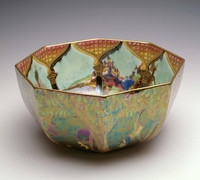 """So-called """"Fairyland Lustre"""" octagonal bowl, outside painted from the Woodland Elves VI series in """"Fiddler in Tree"""": massive tree trunks with branches bearing large green leaves form arches under which fairies play. A fiddler is perched on a branch above leapfrogging elves. Painted in gold, purple, green and pale yellow. Inside painted in """"Ship and Mermaid"""": Mottled pillars supporting ogee arches with a rose-backed grille reveal a type of mediaeval French chateau on a rocky shore and a collection of objects: a galleon in full sail, the head of a crocodile, a mermaid and a dovecote on a small island with two bat-winged figures seated back to back."""