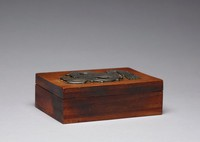 Small rectangular rosewood box with hinged lid, the top with silver inlay in the form of the Mesoamerican serpent god Quetzalcoatl, his body tied in a knot, with feathers extending from his tail and his tongue out.