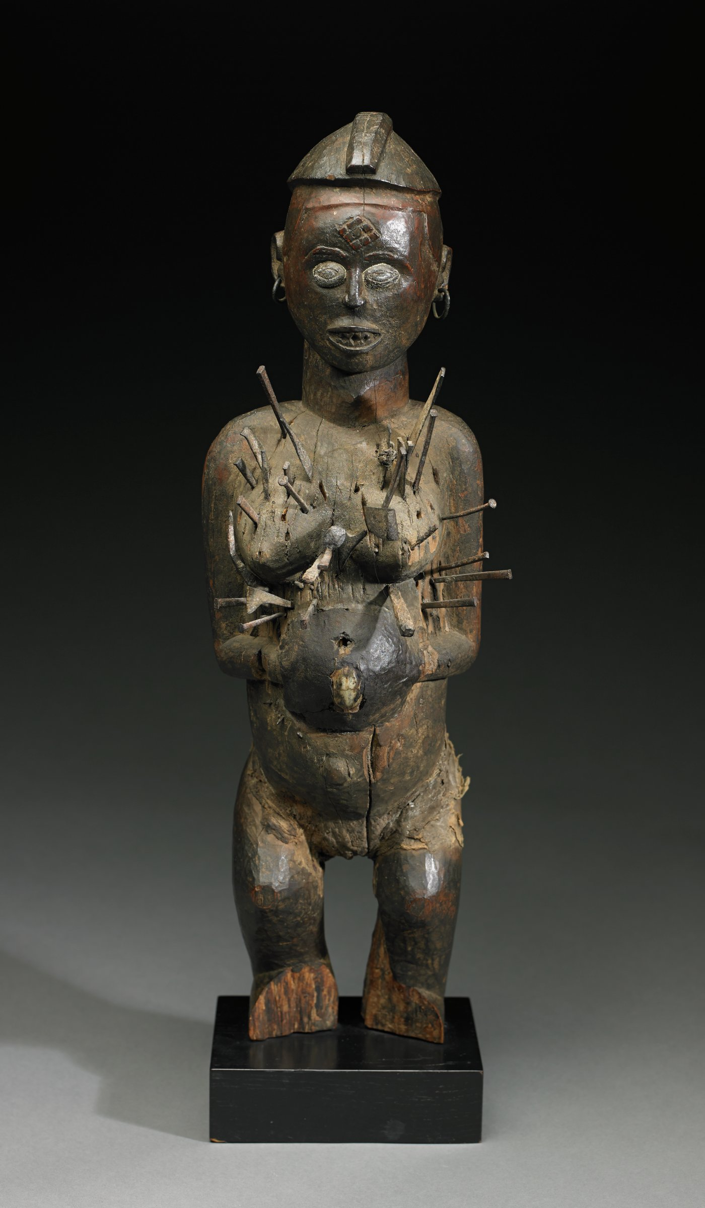 Standing female figure with flexed knees, arms bent, resting on abdomen, wearing small cap, earrings, and with diamond-shaped mark on forehead. Nails and blades protruding from breasts and front of torso, and holes remaining where some nails removed; umbilical area has small animal skull covered over with organic material. Large nail protruding from back of figure, which is split along the spine, from neck to buttocks.