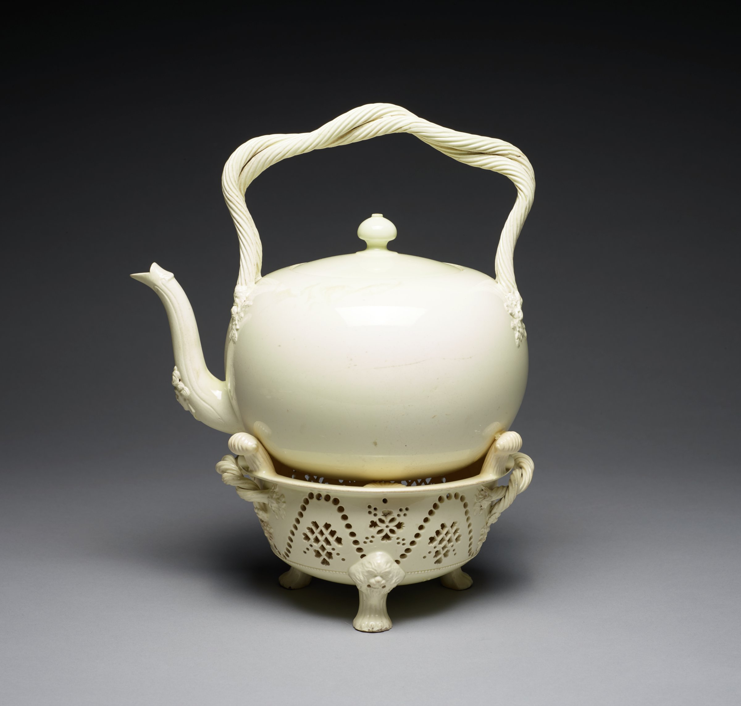 Creamware hot water kettle on stand, the kettle plain and bulbous with double rope, twisted bail handle that terminates on either side in floral heads, the base of the spout is supported by a female head, with flat cover with mushroom finial, the conforming stand of circular form and supported by three masked feet, the body of the stand is embellished with decorative piercing, with two rope twisted handles and three lugs which prevent the kettle from sliding.