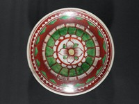 Painted overglaze red and green enamel design of concentric radiating petals within a serrated border. The red enamel is thick and matte, the green enamel is thin and glossy.