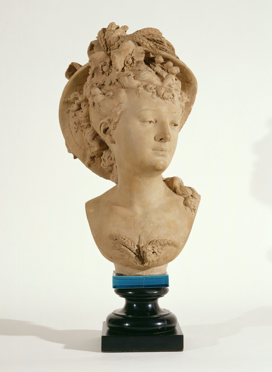 Bust sculpture of autumn personified as a woman. Her hair curled and pulled loosely up under her hat. The hat is decorated with harvest motifs of wheat.