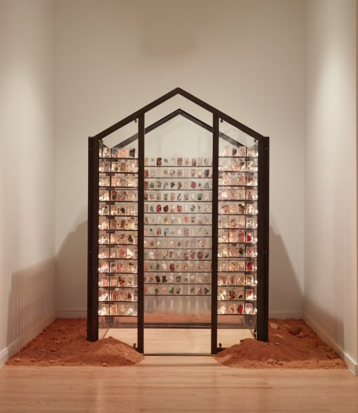 """A four-sided, metal-framed architectural structure with walls of two-sheet Plexiglas. The frame is rectangular with a raised pitch; there is no roof or cover. The front wall contains an open doorway, through which visitors may enter.  Rows of narrow shelves line the walls of the structure. Evenly spaced upon the shelves are small """"bricks"""" of Lucite, within which are suspended bits and pieces of small everyday objects. The shelves are lit so as to make the individual bricks glow. Soil is mounded around the structure's outer perimeter to about a two-foot width. There are shards of crockery and other detritus in the dirt. One hears a soundtrack of recorded voices, mostly one-at-a-time."""
