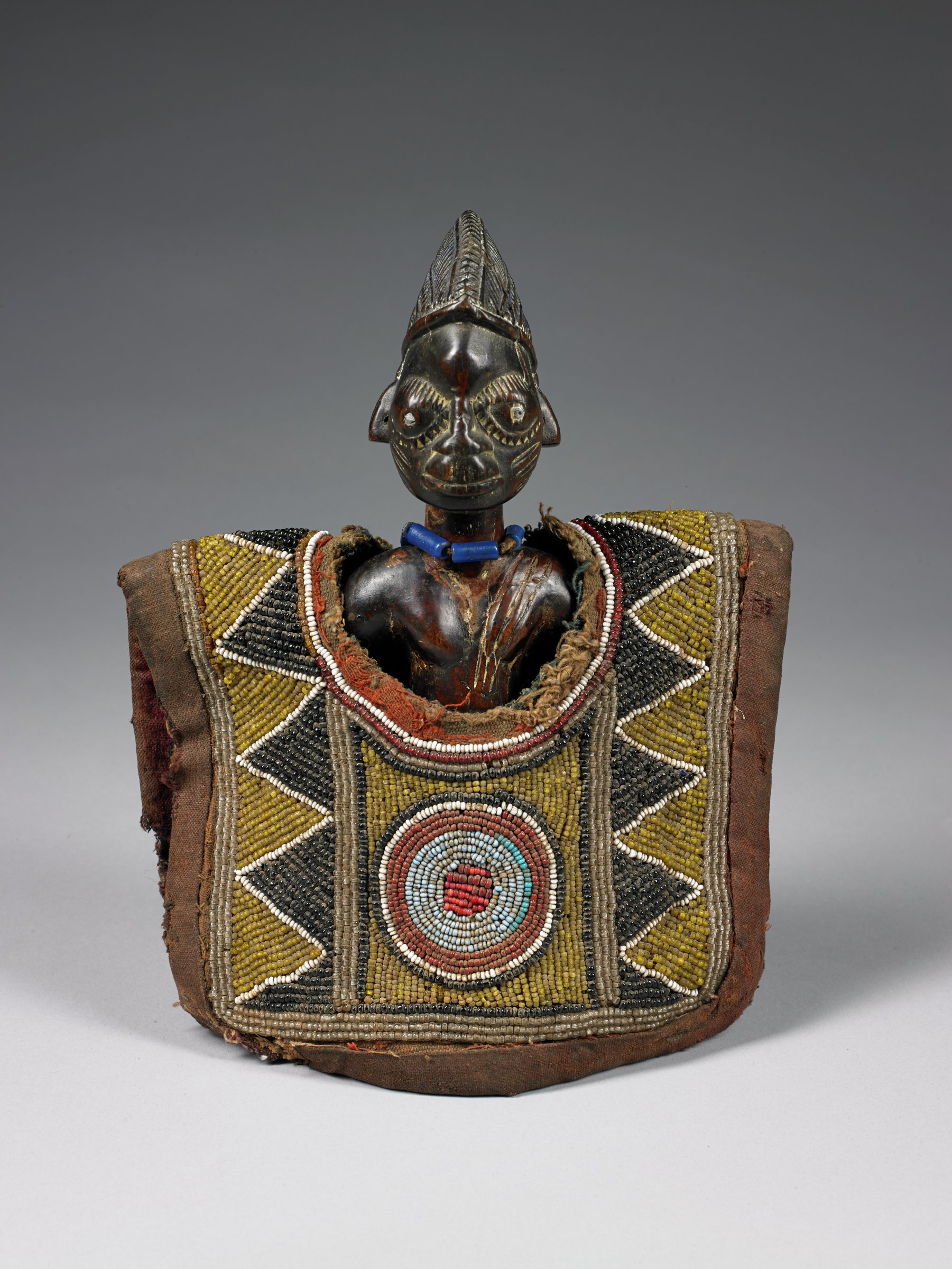 Carved wood figure with beaded vest.
