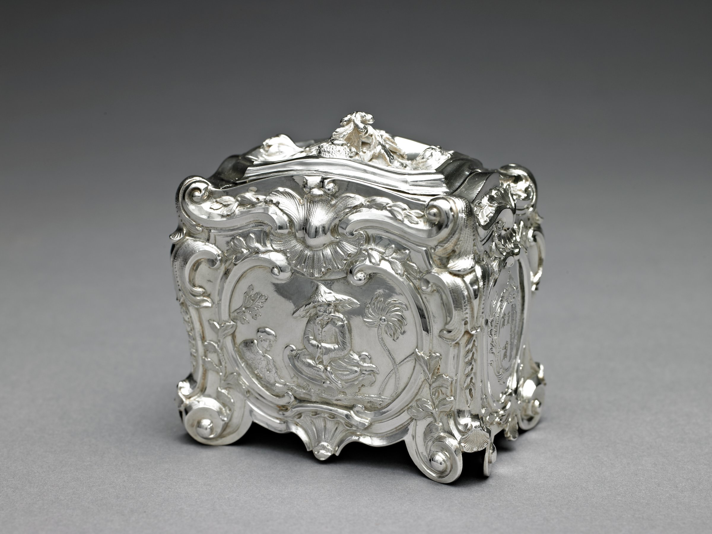 Rectangular tea caddy of heavily carved ivory with silver mounts, the caddy decorated in relief on all sides with images of Chinese figures, exotic scenes, and animals with delicate floral sprays and leaves within a Greek key pattern border, with engraved silver escutcheon and hinges, four silver claw feet, and silver pineapple finial, the interior lined with wood covered with red velvet; the pair of tea canisters of heavily and elaborately chased silver in the Chinoiserie style, rectangular with slightly contoured sides and decorated with scrolls, shell, and leafy motifs, on the sides within a reserve 1) the figure of a seated Chinese figure in robe and hat, sitting on a cushion with palm trees and a second seated figure on the left; and 2) a standing Chinese figure in robe and hat with an architectural structure in the background and exotic trees, with a second standing figure on the right holding a flag or pennant; at both ends an engraved coat-of-arms, the covers with truncated edges and an elaborate finial comprised of flowers, ribbons, and leaves.