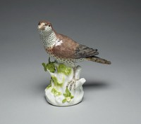 Porcelain figure of a thrush with a white head and brown plumage perched on a low leafy tree stump amidst red berries, blue flowers, brown mushrooms, a puce caterpillar, a beetle and a bee.