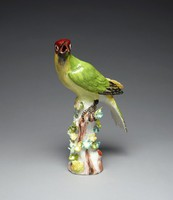 Porcelain figure of a woodpecker perched on a tree stump, with green back feathers, black open beak and black feet.