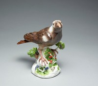 Porcelain figure of a thrush with brown and gray plumage and a brown-speckled white breast perched on a low tree stump heightened in green and yellow and applied with a small branch and yellow florette with green leaves.