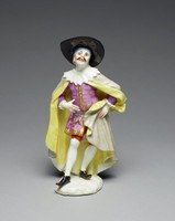 The figure of a mustached Doctor Boloardo standing on a small white base, his knees bent and his right leg thrust forward, his hands at waist, wearing red knee breeches, white stockings and black shoes, his puce-colored coat with gilt buttons and details, a large white ruffled collar rests upon his gray cloak with yellow lining, he wears a large black hat over a blue skullcap
