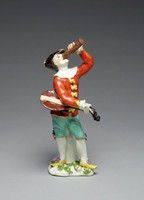 On small base decorated with green leaves stands the figure of Harlequin against a tree stump wearing turquoise knee breeches with lilac florettes and a red tunic with gilt banding, incised scroll design, and yellow bows down the front over a white shirt with ruffled collar and cuffs, on his head rests a gilt-edged tricorn hat with white bow, his shoes are yellow with lilac florettes, under his right arm he holds a lute, his left arm raises a tall pass glass to his mouth