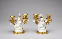 White glazed porcelain two-light candelbra with gilt bronze and a seated chinoiserie figure at center.