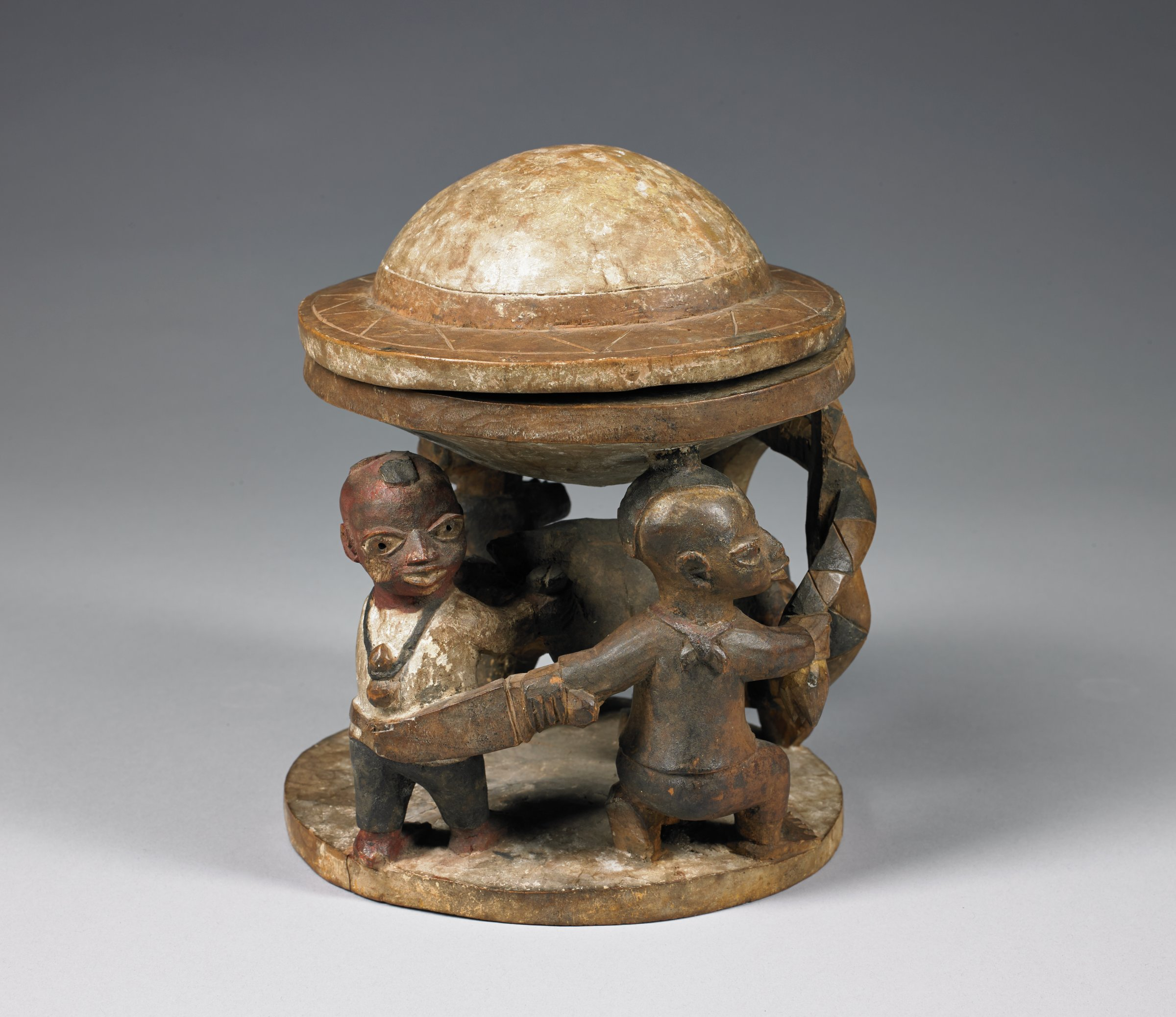 Carved wood bowl with lid carved as a pith helmet, python attacking boar or warthog, with several human figures. Used to hold kola nuts for divination.