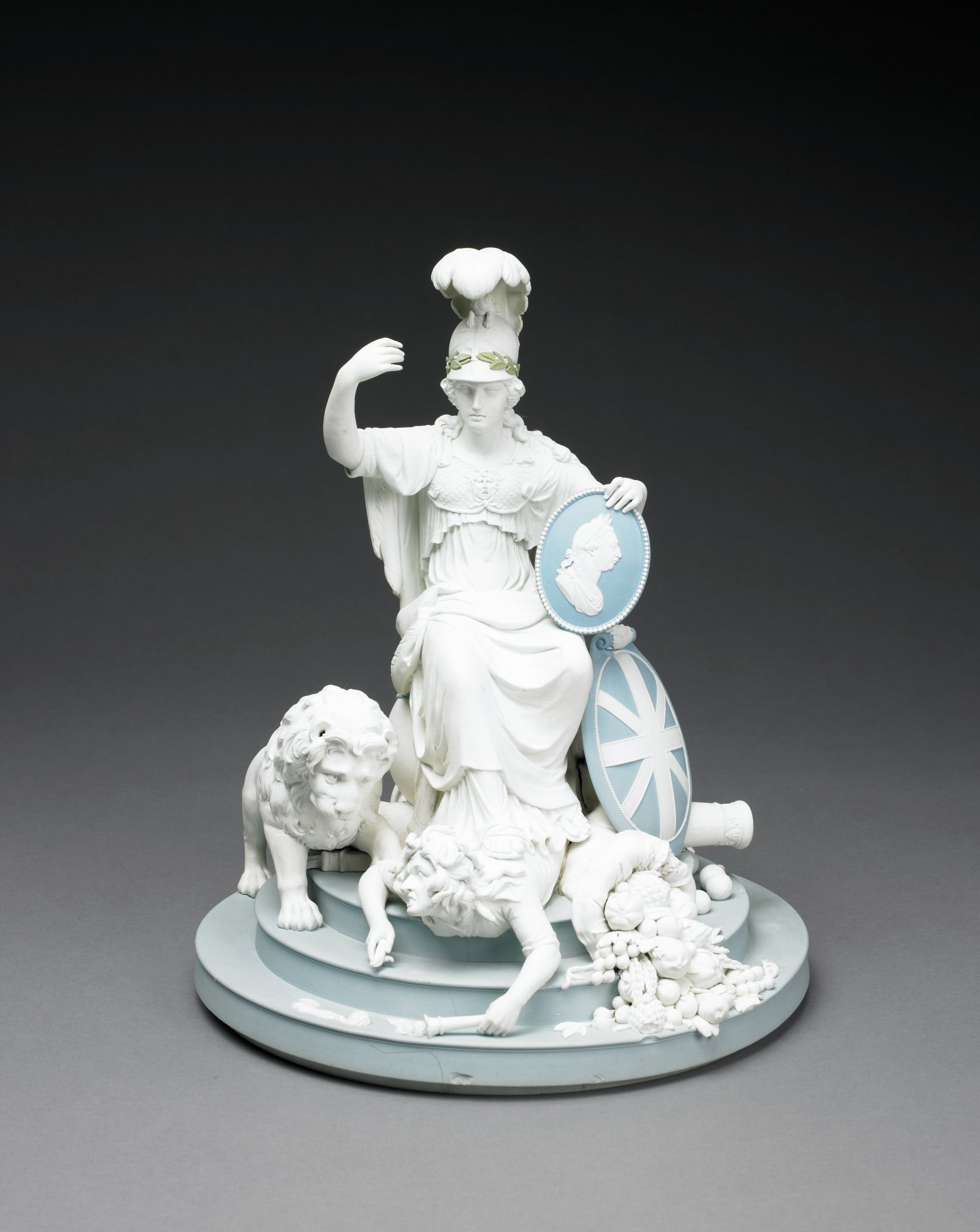 Large group of solid white and solid blue jasper with white and green jasper relief, on a stepped blue base the white figure of Minerva as Britannia Triumphant sits atop a globe encircled in blue with the signs of the zodiac, her helmet is plumed and crowned with a sphinx above a wreath of green laurel leaves; Britannia is draped in a classical gown with cape and wears a breastplate with the winged head of Minerva, her left hand supports a blue and white portrait medallion of King George III as a Roman emperor, which rests on her knee, and her right hand is raised -- it originally held a trident;  Britannia's sandaled feet rest upon France, represented as a distressed and angry fallen female figure of white jasper holding a torch in each hand (the right hand torch is broken, the flame of the left is partially missing), the watchful white jasper British lion stands at Britannia's right, at her left is the blue and white shield of Great Britain as well as a large white cornucopia overflowing with fruits, vegetables, and grains as symbols of strength, victory, and plenty; behind Britannia are various symbols of war and the British navy, all in white jasper: a cannon and cannon balls, a flag, a ship's prow and anchor, a breastplate, helmet, and sword, a shield, and a quiver of arrows.