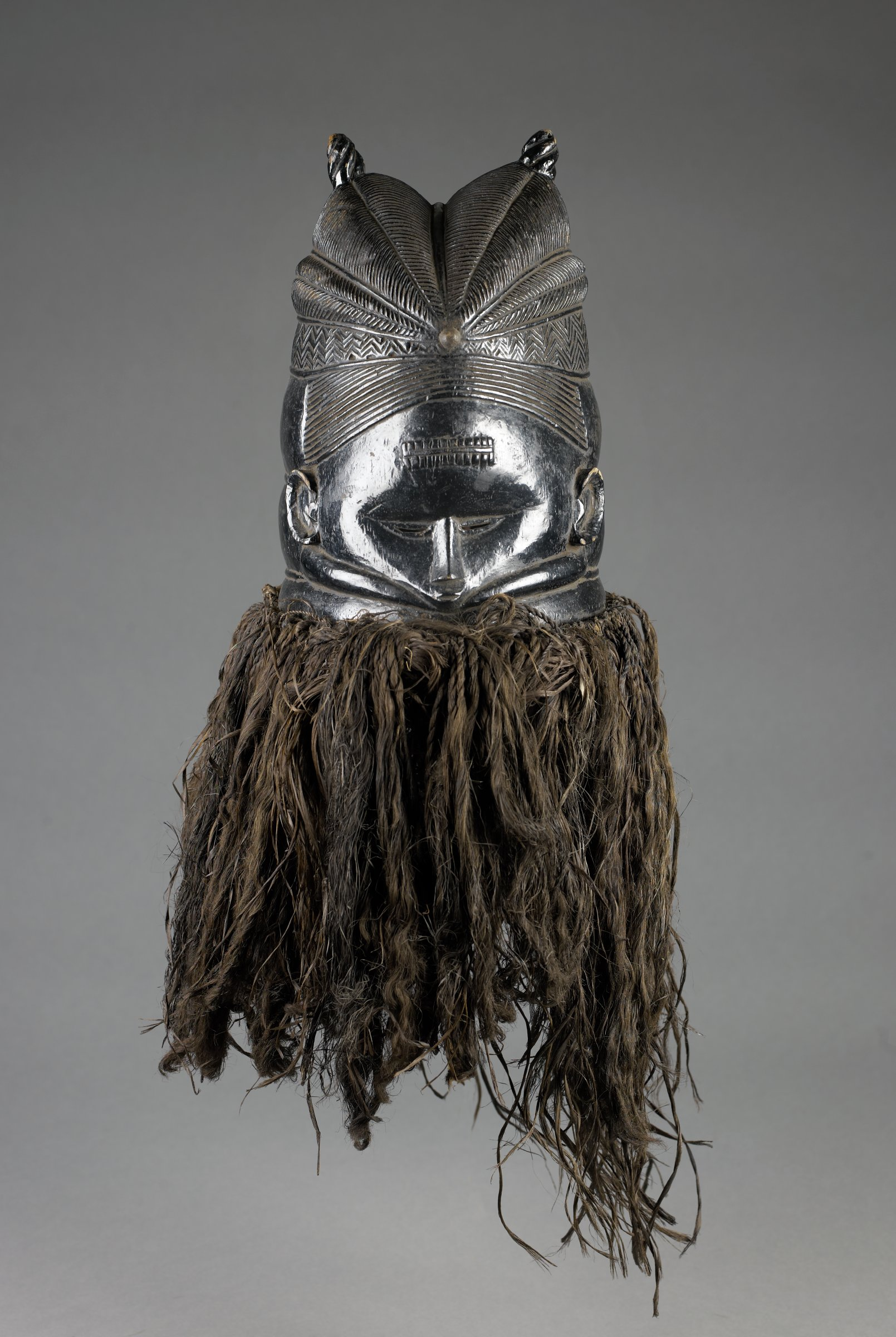 Helmet mask with female face has glossy, black surface, elaborate plaited coiffure, band of horizontal marks on forehead, slitted eyes, bulging rings around neck, and black raffia fringe attached to base.