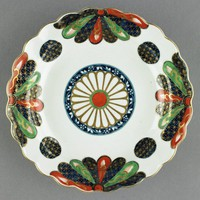 """A soft-paste porcelain plate with scalloped edge decorated in the Imari style with the """"Old Japan Fan"""" pattern, with underglaze blue and overglaze red and green """"fans"""" highlighted in gold on each of the four sides, and with four blue roundels with gold highlights in between, in the center is a large chrysanthemum motif in gold with a red and green center and blue band around, on the underside of the rim is a pattern of trailing floral vines in blue with red floral motifs."""
