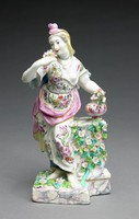 Lady wearing dress and cloak leaning against pedestal, painted with a marblized effect in pink, purples and blue; left hand rests on porcelain covered urn